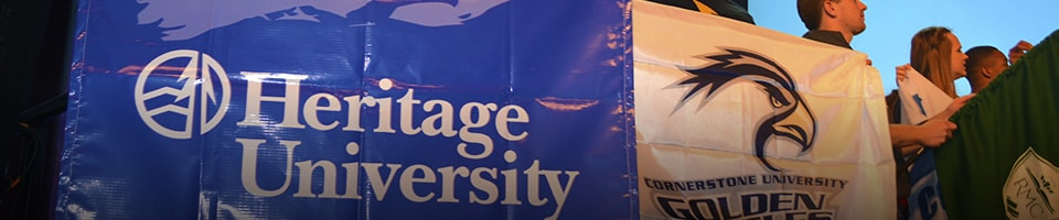 Student holding Heritage University banner on stage