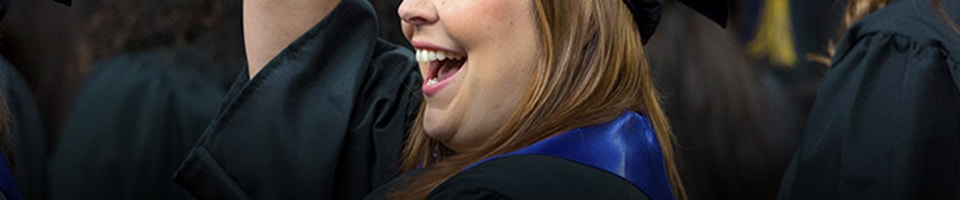 Student waving at crowd during graduation ceremony at heritage university