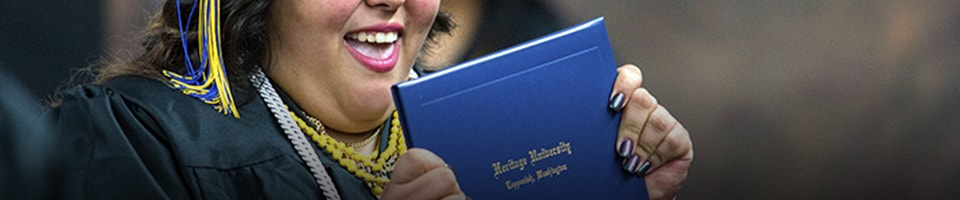 Student showing off degree during graduation ceremony at heritage university
