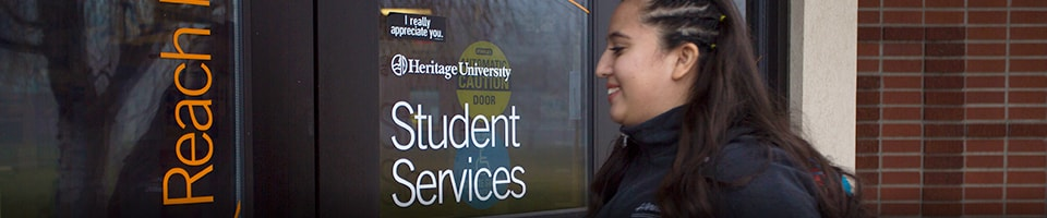Student entering Student services building at Heritage University