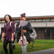 three students walking laughing with each other on heritage campus