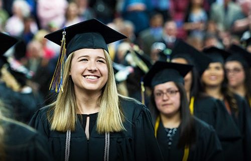 Student smiling looking up at crowd in graduation outfit